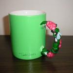 grön mugg med rosa rosor