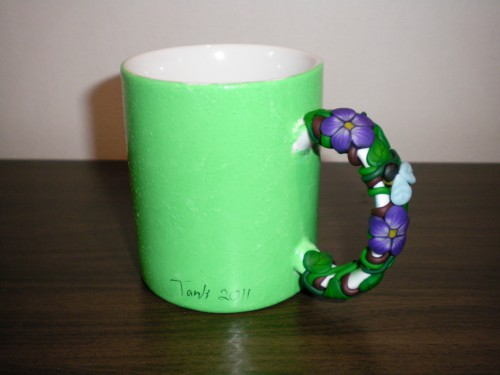 grön mugg med lila violer