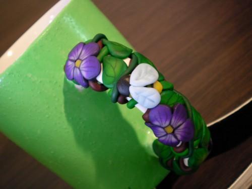 grön mugg med lila violer, närbild